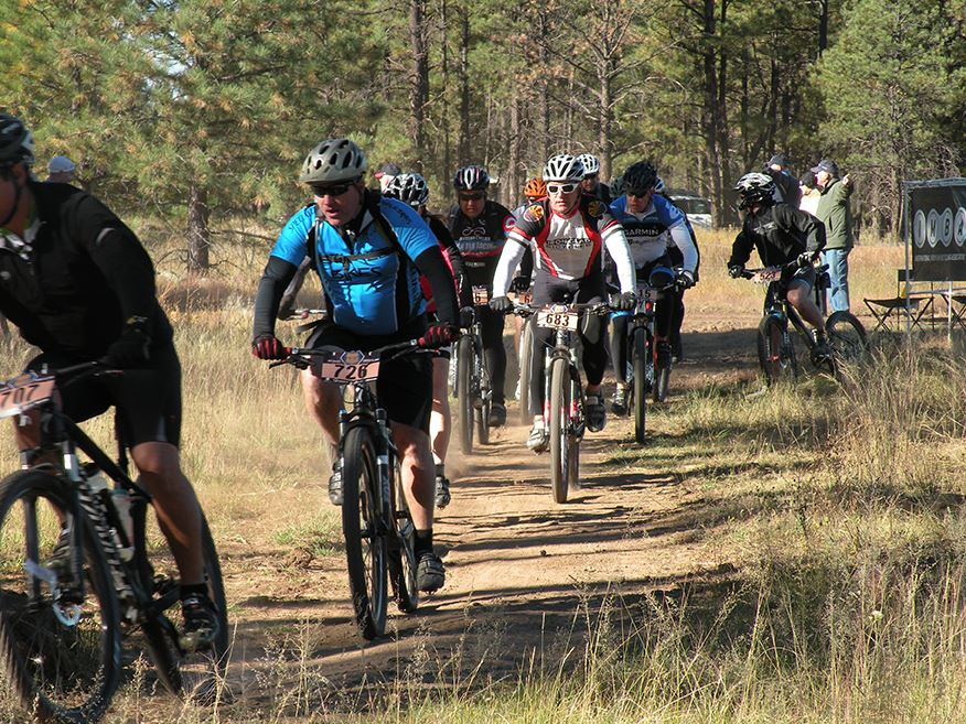 Pack of Bicyclists Racing on Dirt Path