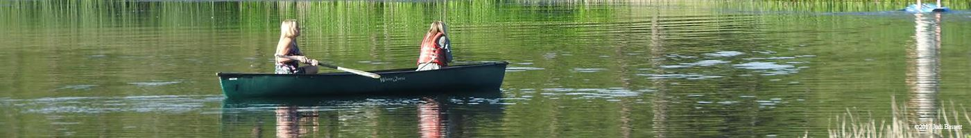 Two People Paddling a Canoe on a Lake