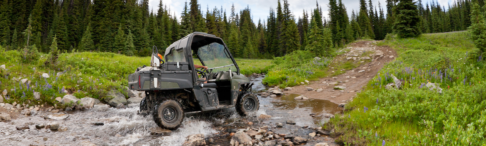 All Terrain Vehicle Riding on a Trail over a Stream