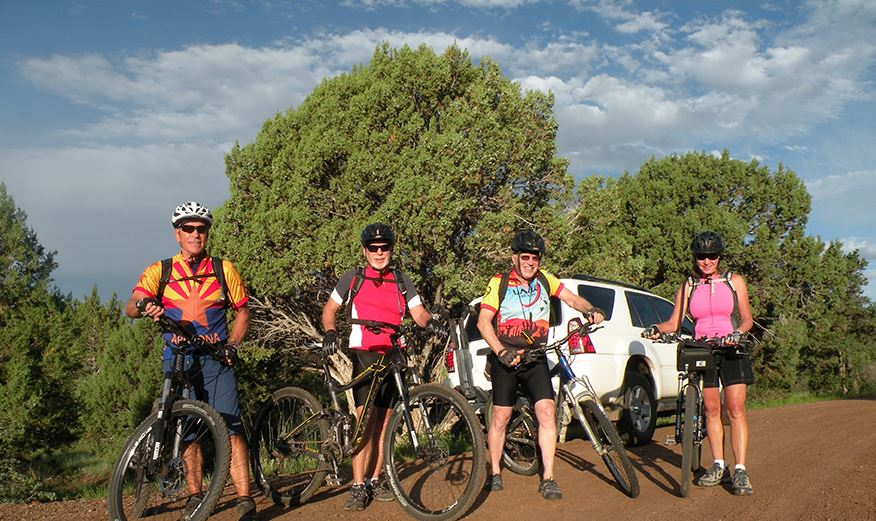 Four Bicyclists Standing by Their Bikes on a Dirt Road