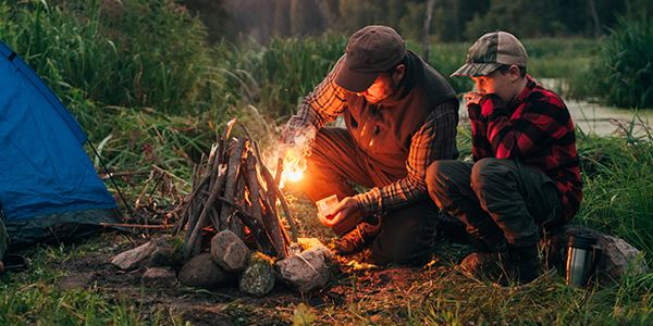 Man and Boy Building a Campfire